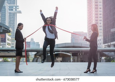 Business woman crosses the finish line or  reaching finish line  to win on city background, business concept.