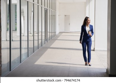Business woman with cup of take out coffee going to work