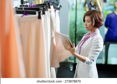 Business woman with a digital tablet choosing skirt in a clothing store
