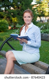 business woman with documents on a bench