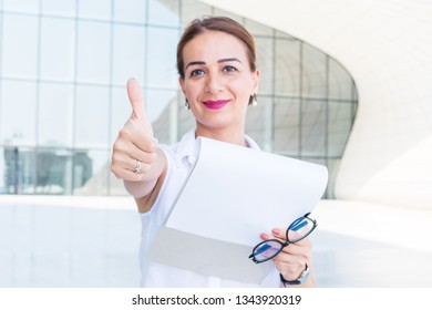 business woman with documents smiles and shows gestures. The Concept Of Success