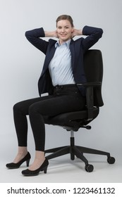 Business woman is doing exercises on office chair