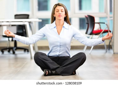 Business woman doing yoga at the office