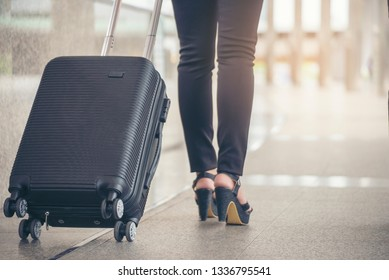 Business woman Dragging suitcase luggage bag,walking to passenger boarding in Airport.Working young woman travel to work.Asian tourist female wearing black suit pull trolley bag.