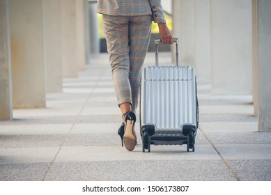 Business woman Dragging suitcase luggage bag,walking to passenger boarding in Airport.Working woman travel to work.Asian tourist female wearing suit pull trolley bag. Businesswoman Travel concept
