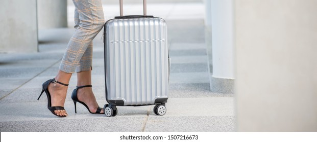 Business woman Dragging suitcase luggage bag,walk to passenger boarding in Airport.Working woman travel to work,wear suit pull trolley bag. Businesswoman Travel concept-panoramic banner for web header