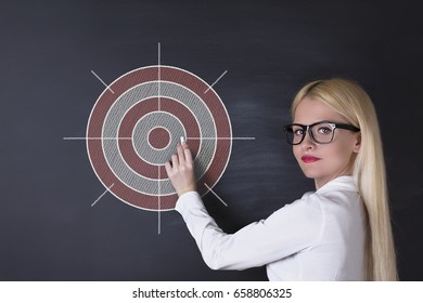 Business woman draw target on the blackboard