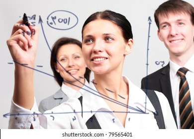 Business woman drawing a graph on a glass window in an office