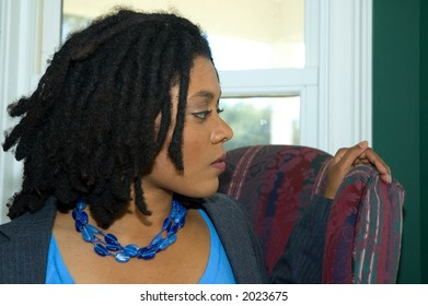 Business woman with dreadlocks, looking to the side.