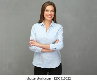 Business woman dressed in blue shirt standing in front of grey wall back.