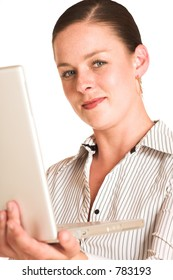 Business woman dressed in a white pinstripe shirt. Wordking on laptop.  Shallow DOF - laptop out of focus, face in focus