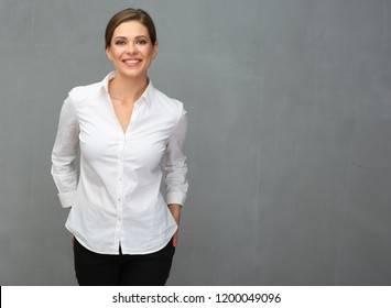 Business woman dressed white shirt standing in front of grey wall back.