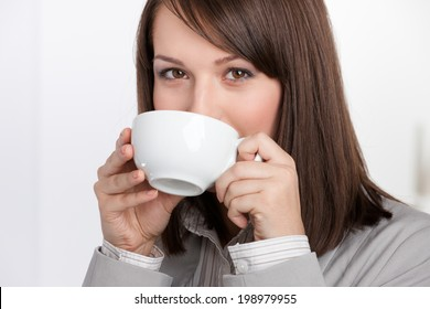 Business woman drinking tea from white cup, isolated on white