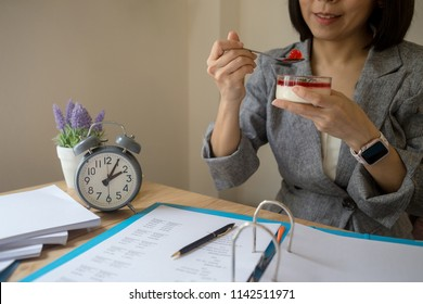 Business woman eat Dessert on the table in the afternoon at the office.