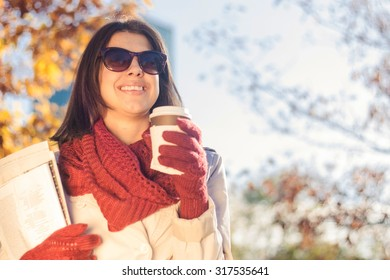 Business woman eating breakfast in autumn park