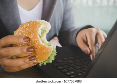 business woman eating junk food burger while working on computer laptop, unhealthy lifestyle concept