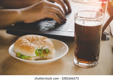 business woman eating junk food burger and cold drink while working on computer laptop at office desk, unhealthy lifestyle concept