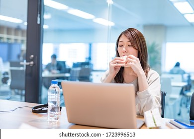 Business woman eating sandwich in meeting room at lunchtime