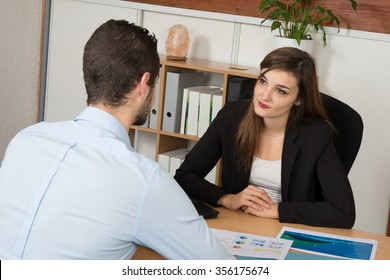 Business woman explaining something to a man at office