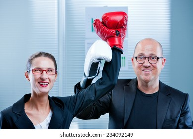 business woman exulting after a symbolic boxe match against a plump businessman endorsing her as a winner