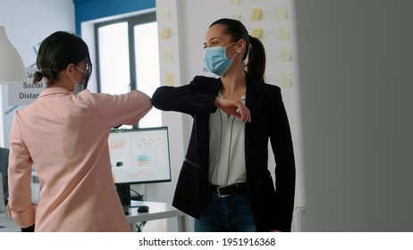 Business woman with face mask touching elbow to prevent coronavirus infection. while working at company office. Coworkers respecting social distancing during covid19 global pandemic