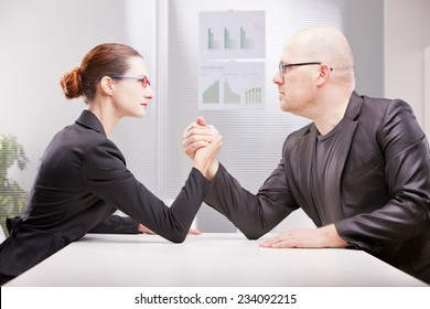 business woman facing business man and starting to perform an arm wrestling to decree who's best