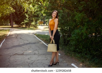 business woman with a fashionable bag in her hands posing on the nature in the park