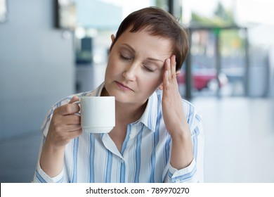 Business woman feeling stressed from work in the office. Middle aged female having headache and drinking coffee or tea