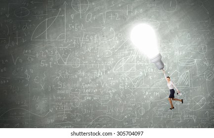 Business woman is flying away on bright light bulb