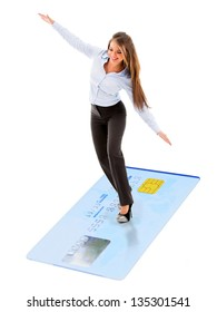 Business woman flying on credit card as a magic carpet - isolated