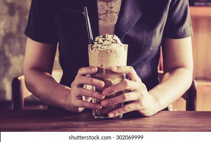 business woman and frappe cappuccino or mocca coffee drink with glass mug in her hand with happy moments vintage color tone style