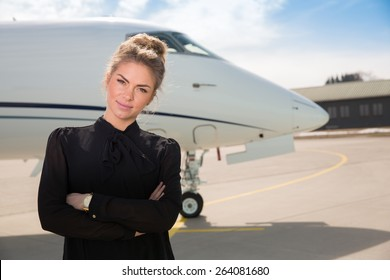 business woman in front of a corporate jet