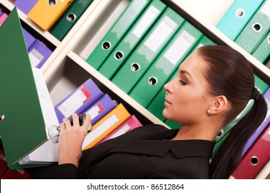 Business woman in front of shelves with folders