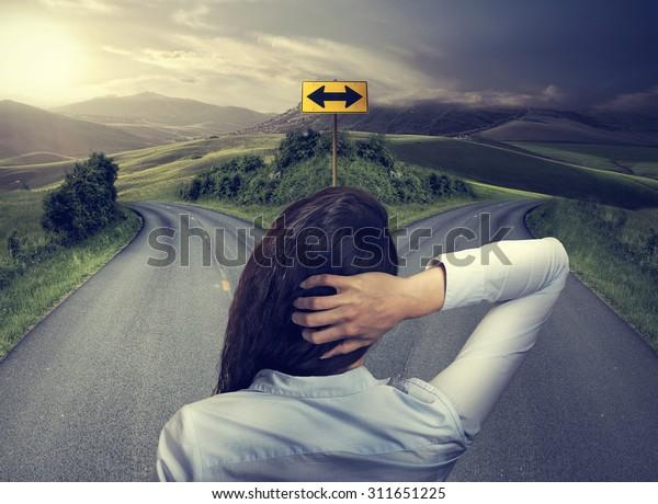 mulher de negócios na frente de duas estradas pensando decidir na esperança de melhor chance de tomar