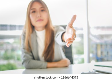 Business woman giving her hand for handshake to partner ,partnership deal successful concept.
