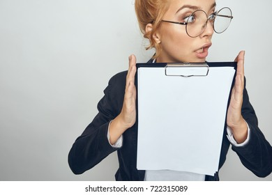 business woman with glasses looking away in hands holding a folder of paper on a gray background, work, business