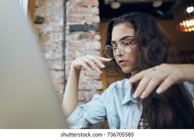 business woman with glasses looking at laptop