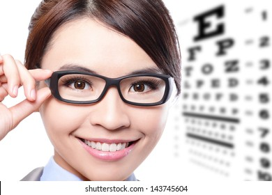 business woman with glasses on the background of eye test chart, eye care concept, asian beauty