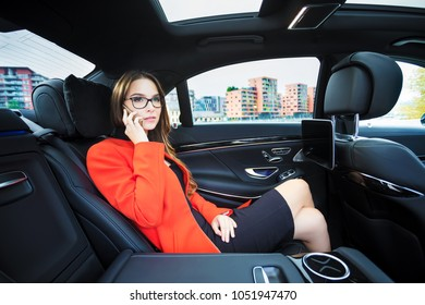 Business woman with glasses and red coat is calling in the luxury car