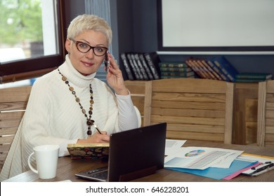 Business woman in glasses sitting at her workplace in the office. She is working on a financial project, graphics, laptop, reports.