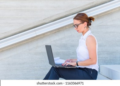 business woman with glasses sitting with laptop on the stairs