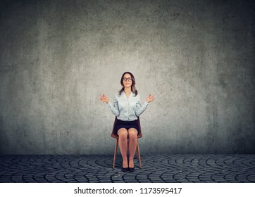 Business woman in glasses sitting on chair and holding hands apart in meditation and harmony keeping eyes closed.