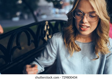 business woman with glasses smiles sitting on a bench outside