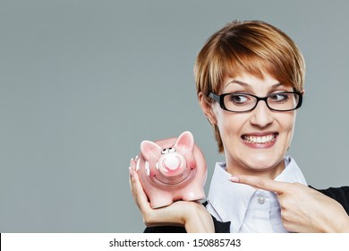 Business woman with glasses smiling and pointing finger to her piggy bank isolated on grey