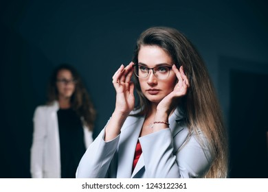 business woman with glasses in a white jacket on a blue background. Team .