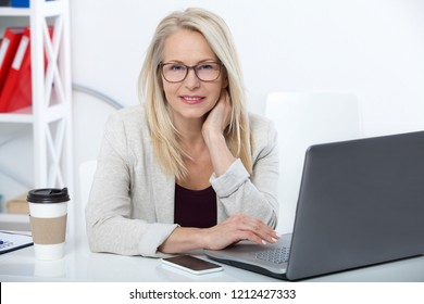 Business woman with glasses working in office with documents. Beautiful middle aged woman looking at camera with smile while siting in the office.