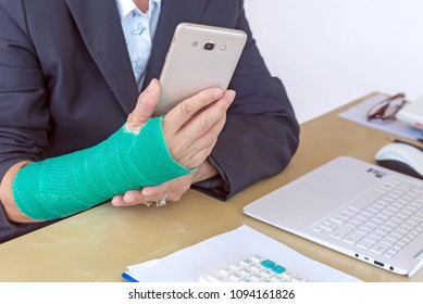 business woman with green cast on arm holding smart phone and working on laptop in office, focus on broken hand.
