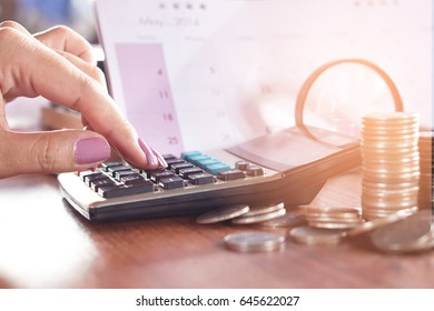 business woman hand calculating her monthly expenses that including coin, magnifying glass and calendar on wooden table