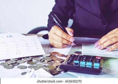 business woman hand calculating her monthly expenses during tax season with coins, calculator, credit card and account bank, idea for dept collection background