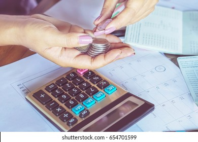 business woman hand calculating her monthly expenses during tax season with coins, calculator and account bank, idea for dept collection background